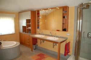 Badezimmereinrichtung aus Birnbaum, Hängeregal mit Spiegeltüren. Obere Schrankfronten mit Edelstahl-Schichtstoff belegt.