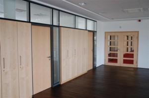 Eine Vollglastrennwand als Büroabtrennung mit integrierten Büroschränken. Schränke und Türen kanad. Ahorn furniert, Oberfläche natur lackiert. Passend dazu ein doppelflügliches Eingangselement mit Glasaussschnitten.