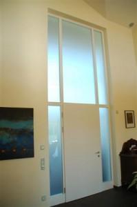 Windfangelement, Türblatt und Rahmen weiß lackiert, verglast mit satinierten ESG-Glasscheiben.