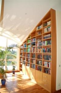 Bücherregal raumhoch, in die Dachschräge eingebaut. Birnbaum furniert, natur lackiert.