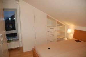 Kleiderschrank im Schlafzimmer, der Dachschräge angepasst, Oberfläche weiß lackiert.