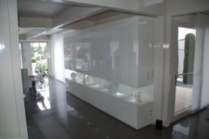 Wohnzimmermöbel mit Unterbau und hängendem Oberschrank. Mittlerer offener Bereich mit LED - Spots beleuchtet. Türen und Außenseiten auf Gehrung. Beleuchtetes Barfach mit Spiegelrückwand und Auszug. Gesamtes Möbel Weiß Hochglanz lackiert.
