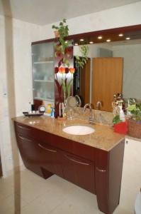 Waschtisch mit Aufsatz und Lampenboard über dem Spiegel. Unterbau als Auszüge mit gebogenen Fronten. Oberfläche Mahagoni furniert, natur lackiert.