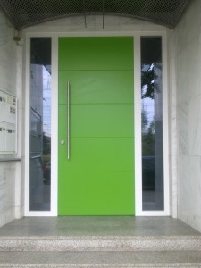 Hauseingangselement mit 2 verglasten Seitenteilen. Türblatt mit 4 Querfugen und senkrechter Edelstahl Griffstange. Die grüne Farblackierung wurde an die vorhandenen Fensterläden angepasst.