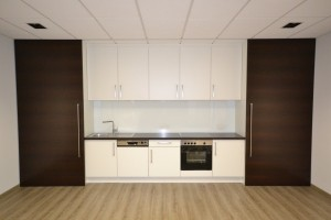 Teeküche in einem Aufenthalts- / Besprechungsraum in Wenge und Weiß kombiniert, passend zur Empfangstheke. Die beiden raumhochen Schiebetüren lassen sich komplett vor die Küchenzeile schieben. Dahinter befindet sich - neben einem Kühlschrank - viel Stauraum.